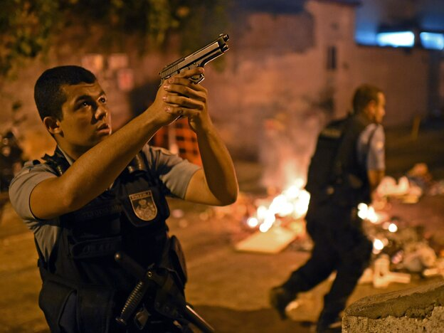 An officer from Brazilian Police Special Forces took aim Tuesday during the violent protest that broke out in one of Rio de Janeiro's slums. People there bl