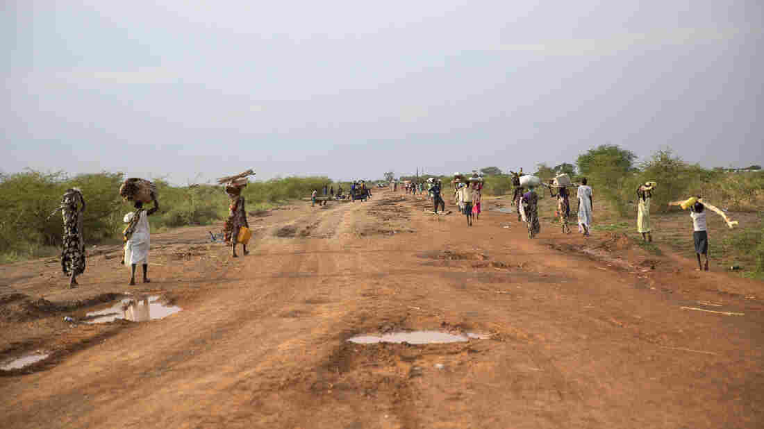 South Sudanese civilians flee from attacks in the northern town of Bentiu on Sunday. Hundreds of civilians were reportedly killed by a rebel group that took the town.