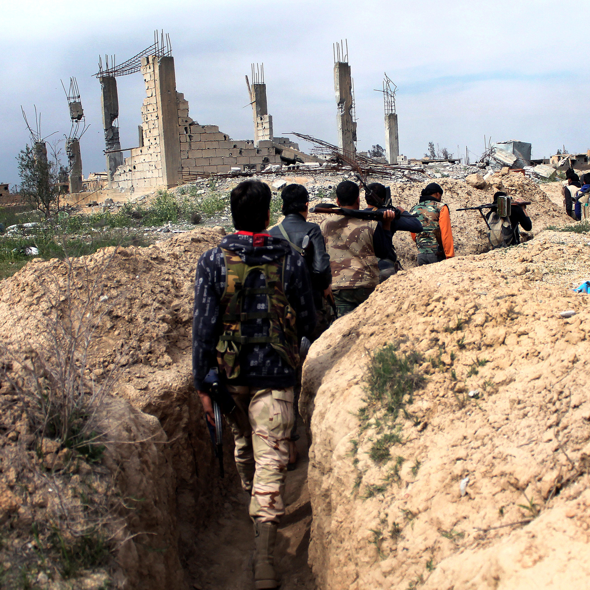 Rebel fighters carry their weapons along a trench in the northeastern city of Deir Ezzor on March 24. The CIA is stepping up training and military assistance to moderate rebels, according to U.S. sources.