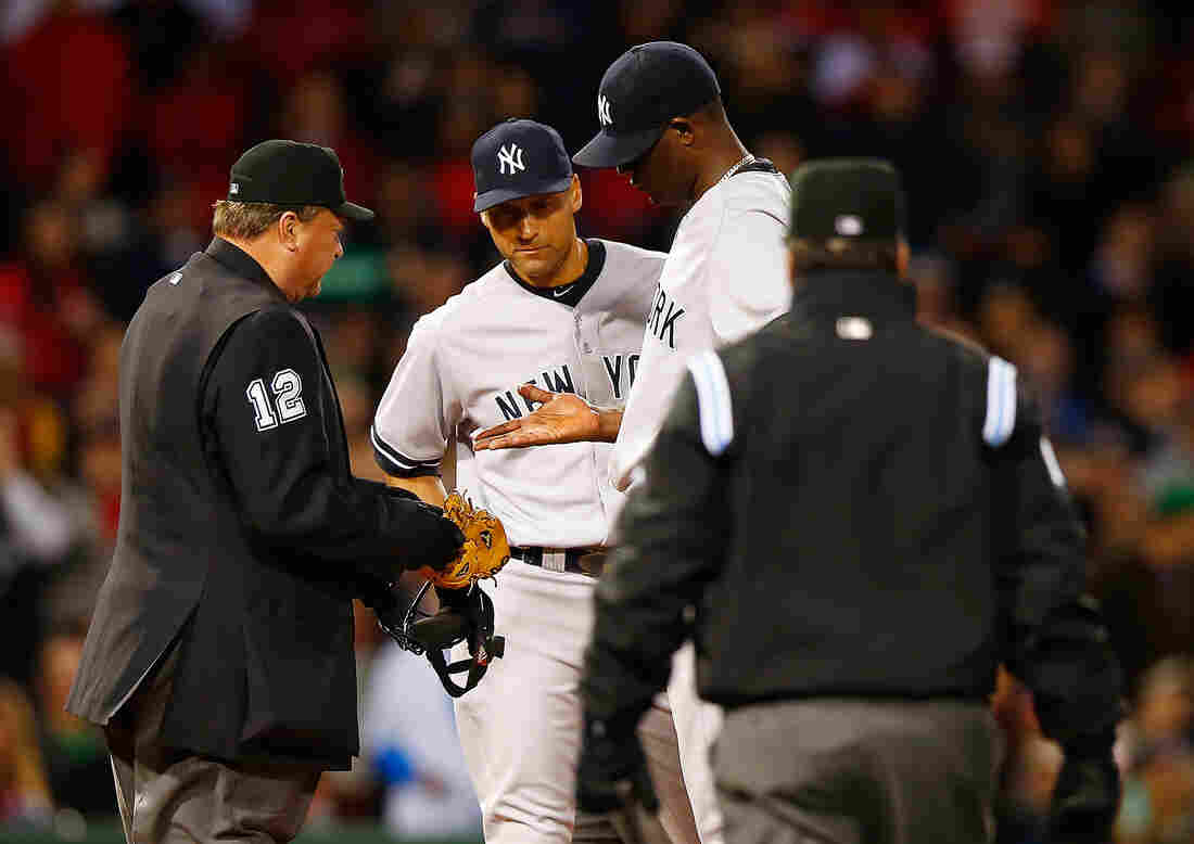 Home plate umpire Gerry Davis checks out the hand of Michael Pineda of the New York Yankees in front of teammate Derek Jeter before throwing him out of the game in the second inning against the Boston Red Sox.