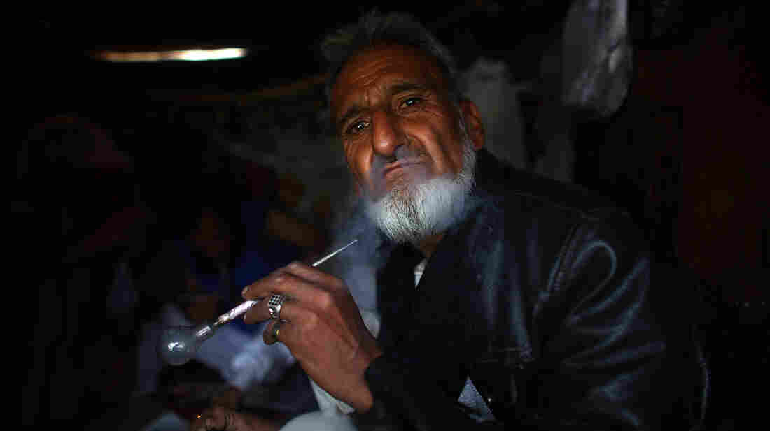 A self-proclaimed poet and scholar, Haji Ismatullah blows smoke out after taking a hit of crystal meth. He says he turned to drugs after his wife and kids were killed in a car accident.
