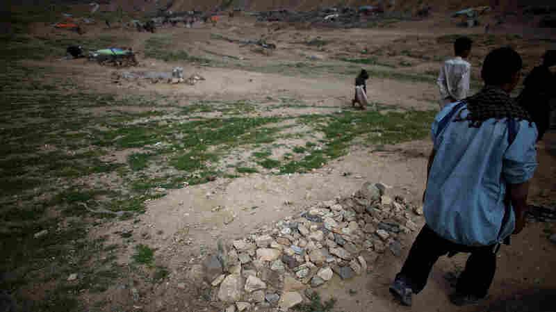 A man walks past a fresh grave in the Kamar Kulagh slum outside of Herat.