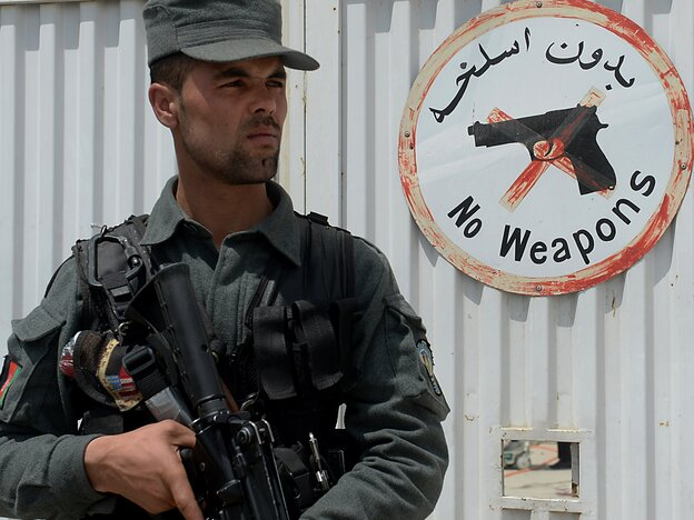 An Afghan police officer kept watch Thursday at the gate of the Cure hospital in Kabul. Earlier,