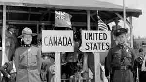 """A Royal Canadian Mounted Police officer stands in front of a sign marked """"Canada,"""" beside an American state trooper."""