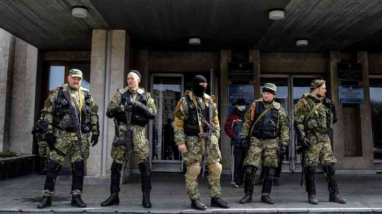 Armed pro-Russian activists stand outside the Ukrainian regional administration building in the eastern Ukrainian town of Slovyansk, on April 14.