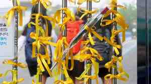 Yellow ribbons hang from a fence outside Danwon High School in Ansan, South Korea, as some students return Thursday for the first time since a ferry disaster claimed the lives of scores of their classmates.