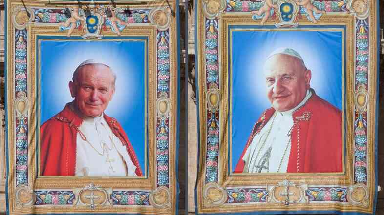 Tapestry portraits of Pope John Paul II (left) and Pope John XXIII hang from balconies on the facade of St. Peter's Basilica in Rome. On Sunday, the two pontiffs will officially be declared saints.