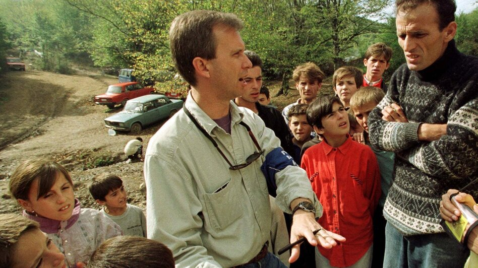 Ron Capps talks with refugees in the Kisna Reka refugee camp some 15 miles from Pristina, Kosovo, in 1998. In his role as a U.S. diplomatic monitor, Capps traveled through Kosovo gathering intelligence from refugees and Serb forces about the situation in the region.