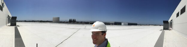 "Paul Hopkins of DuPont Fabros stands on the roof of company's newest Silicon Valley data center. ""It's about the same size and length as a Nimitz aircraft carrier,"" he says."