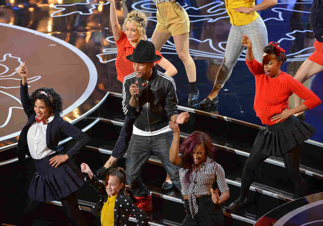 """Pharrell Williams (center) performs """"Happy"""" at the 2014 Oscars in Los Angeles."""
