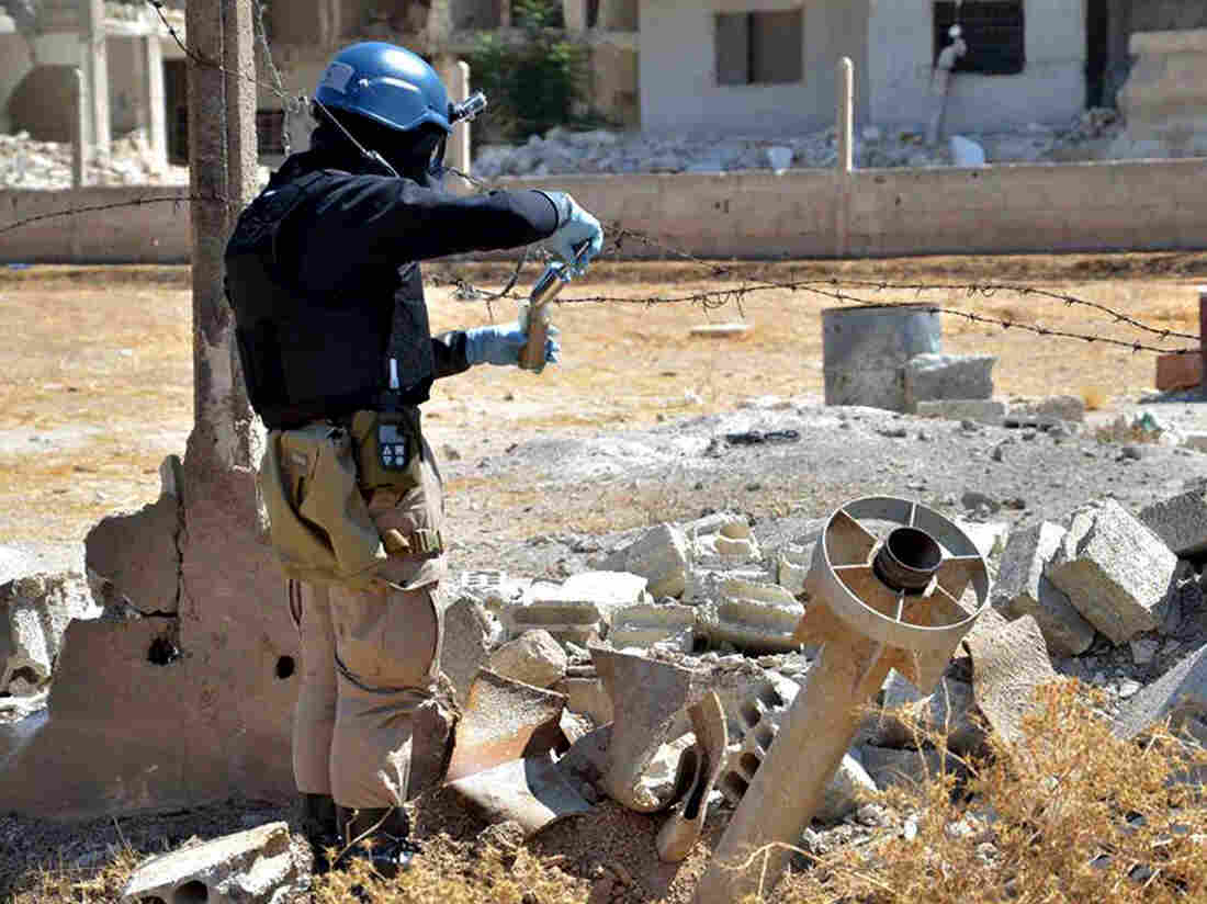 A member of a U.N. investigation team collects samples of sand near part of a missile used in the deadly chemical attacks on Ghouta, on Aug. 28, 2013.