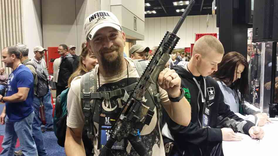Ben Pickering shows off a new Ambush AR-15 rifle after winning a drawing at the NRA annual meeting in Indianapolis on Friday.