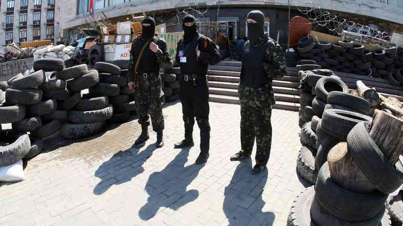 "Masked pro-Russian activists guard a barricade outside the regional state building seized by separatists in the eastern Ukrainian city of Donetsk Saturday. Pro-Russian forces holding a group of international observers have accused them of being ""NATO spies."""