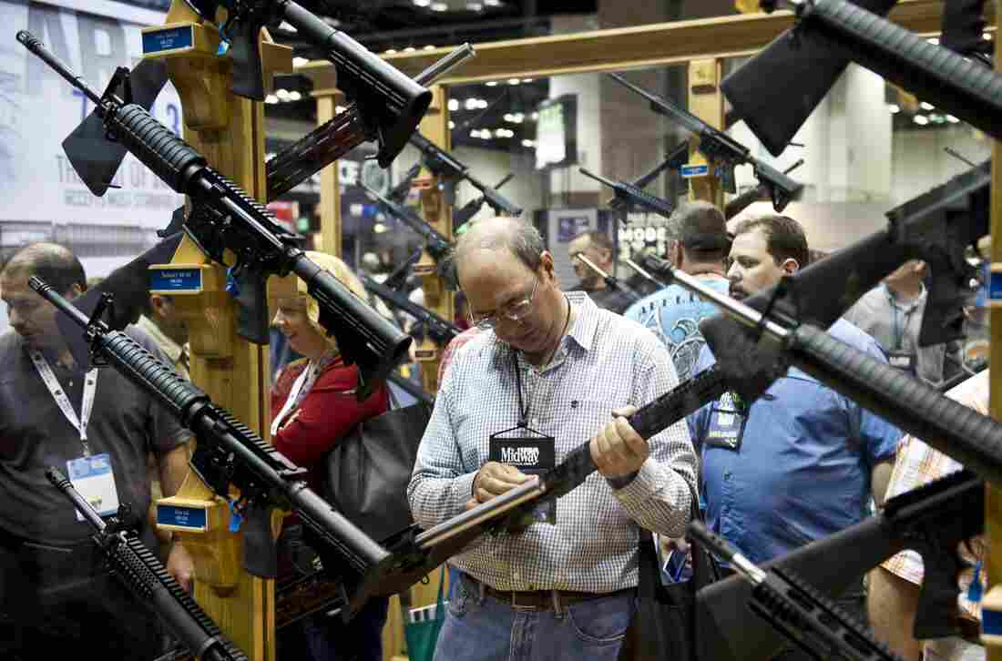 A man examines weapons in the exhibit hall at the 143rd NRA Annual Meetings and Exhibits at the Indiana Convention Center in Indianapolis.