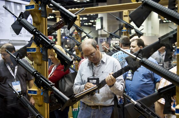 A man examines weapons in the exhibit hall at the 143rd NRA Annual Meetings and Exhibits at the Indiana Con