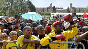 People attend South Africa's Freedom Day celebrations in Pretoria, with the federal Union Building in the background Sunday. The day marks the end of the apartheid era, when all races went to the polls to vote in historic 1994 elections.