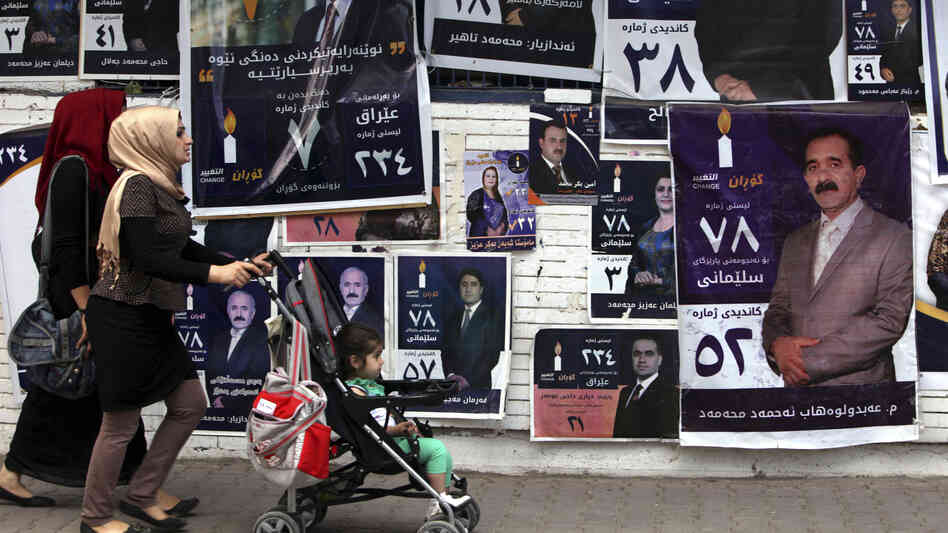 Iraqis walk past parliamentary campaign posters in Sulaimaniya, northern Iraq, on Monday. The national election on Wednesday is the first since the withdrawal of U.S. troops.