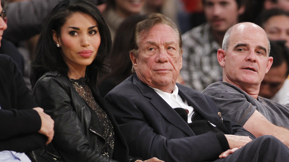 Los Angeles Clippers owner Donald Sterling (center) has been banned by the NBA; he is seen here watching a Clippers game with former girlfriend V. Stiviano. (AP)