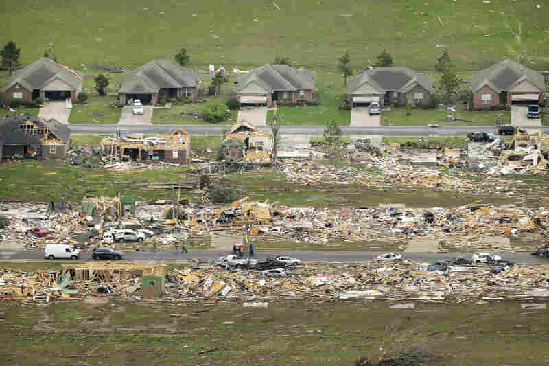 A row of lightly damaged houses faces homes that were destroyed by a tornado in Vilonia late Sunday.
