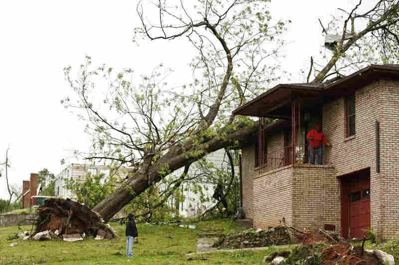 A tree leans against a home in Bessemer, Ala. Sunday was the three-year anniversary of a major tornado outbreak that killed more than 250 people in six states, including Alabama and Mississippi.