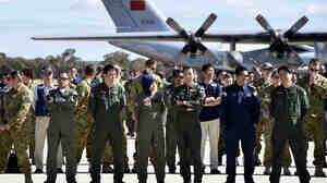 International air crews involved in the search for the missing Malaysia Airlines plane gathered Tuesday on the tarmac at the Royal Australian Air Force Pierce Base in Bullsbrook, near Perth.