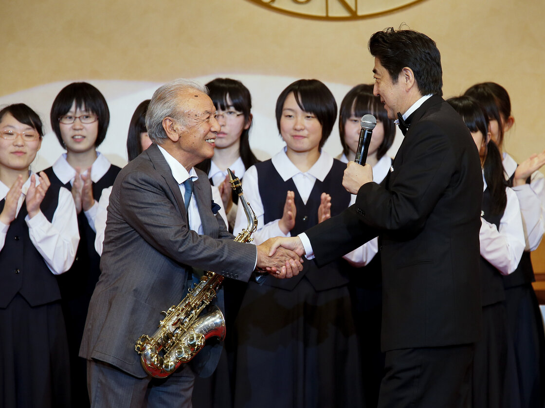 Japanese Prime Minister Shinzo Abe celebrates with saxophonist Sadao Watanabe after performing with high-school students from Fukushima in northern Japan in 2013.