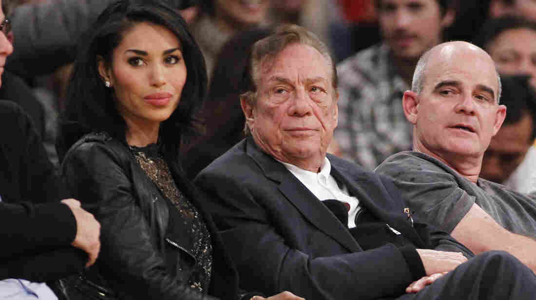 Los Angeles Clippers owner Donald Sterling (center) has been banned by the NBA; he is seen here watching a Clippers game with V. Stiviano in 2011.