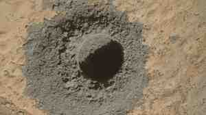 The rover has drilled a hole in sandstone. It will soon collect samples to learn more about how the rocks formed.