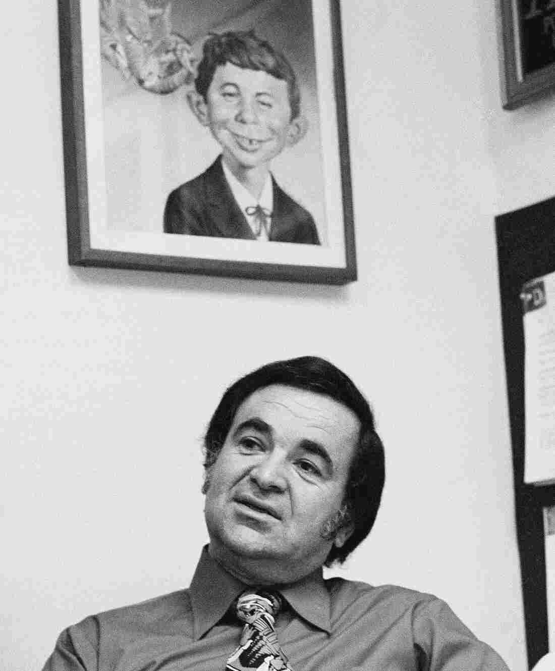 Editor Al Feldstein works on page layouts in his office at Mad magazine's New York headquarters in 1972. A poster with the iconic character Alfred E. Neuman hangs on the wall behind him.