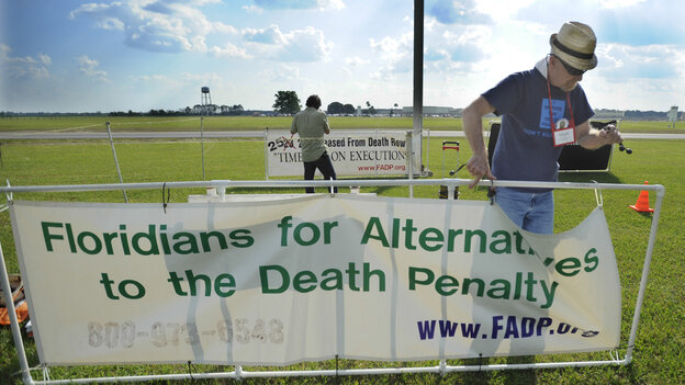 Death penalty opponents set up signs April 23 at the Florida State Prison near Starke, Fla., just hours before the execution of Robert Eugene Hendrix, 47, who killed his cousin and his cousin's wife to prevent him from testifying in a burglary case against him.