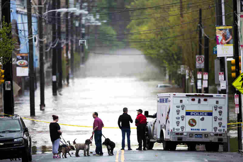 People gather to view floodwaters from the Schuylkill River in Philadelphia. Flood warnings Thursday stretched from Mississippi to Massachusetts.