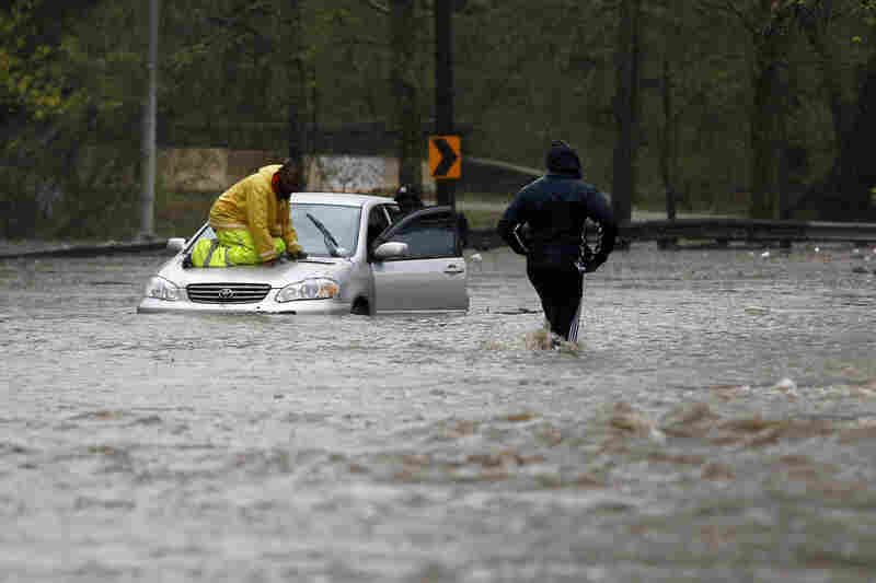 A man walks across a flooded section of Cobbs Creek Parkway as a tow truck worker tries to free a swamped car in Philadelphia.
