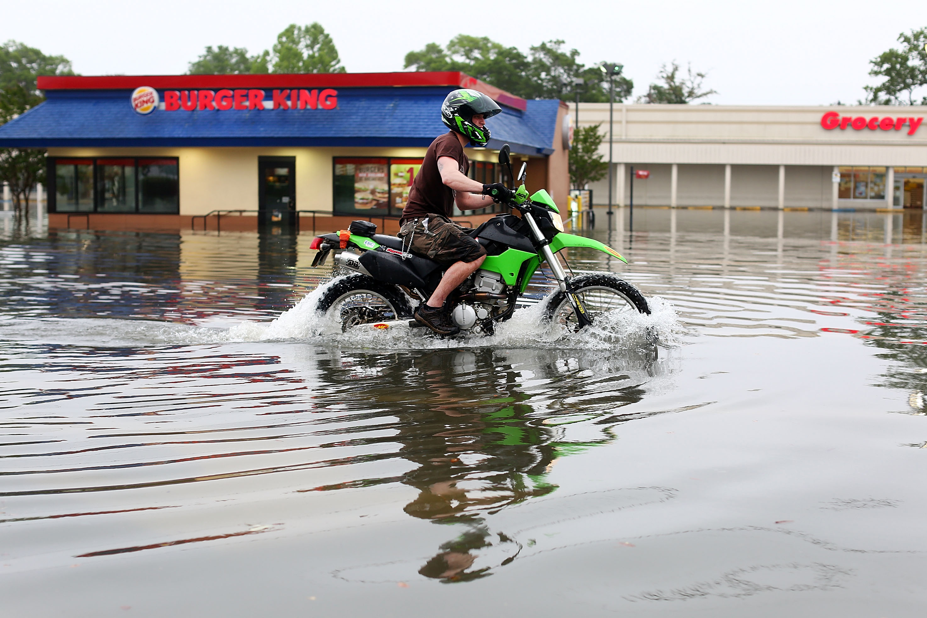 A man rode a motorcycle on a flooded street in Pensacola. Wednesday marked the single rainiest day ever recorded in the city.