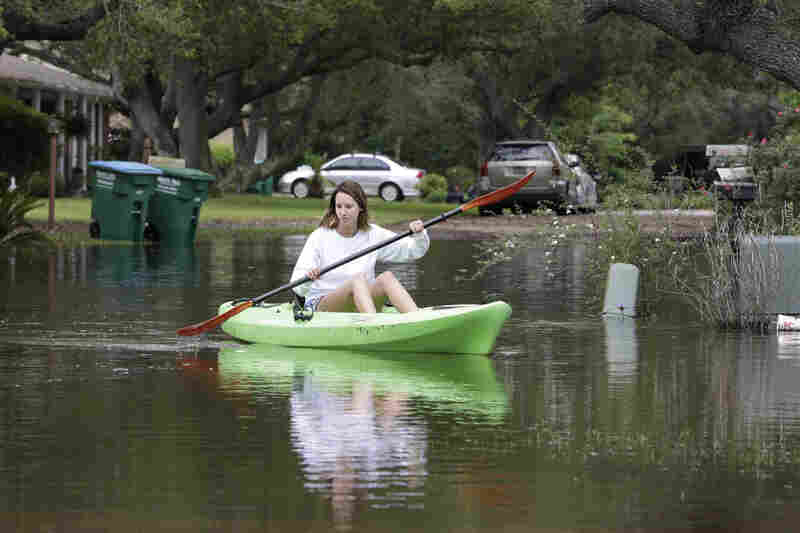 Chelsea Owens navigates a kayak down a flooded street near her home in Gulf Breeze, Fla., on Thursday. Much of the East and parts of the South have been hit by torrential rains. Florida's Panhandle and southern Alabama, for example, got about 2 feet of rain in 24 hours.