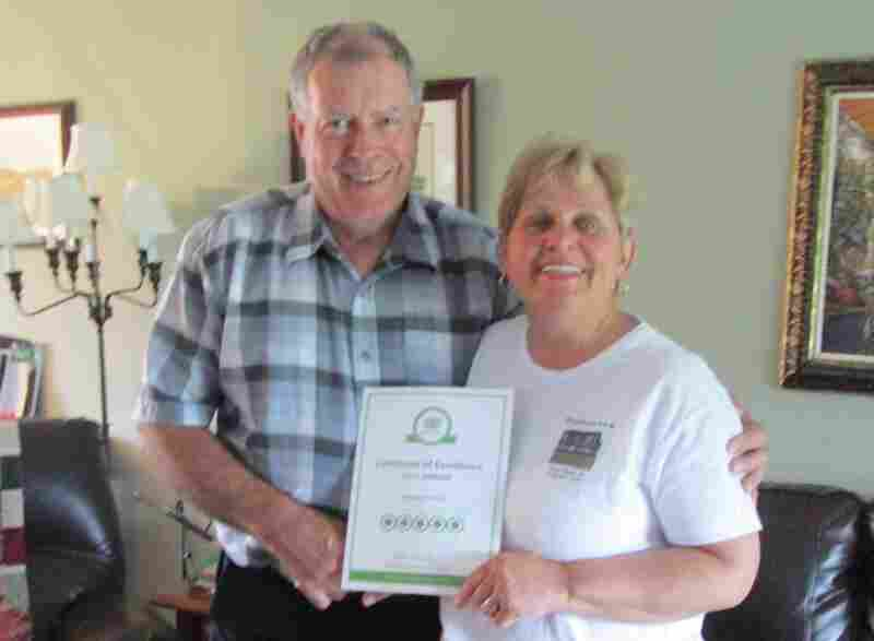 The beached whale in Newfoundland has been a blessing for Tom and Doris Sheppard's local business. Here, they hold a 5-star review of their B&B from TripAdvisor.