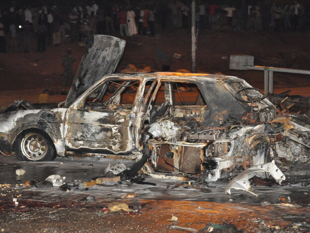 A destroyed car is seen at the blast site in Nigeria's capital, Abuja, on Thursday. The death toll rose to 19 on Friday.