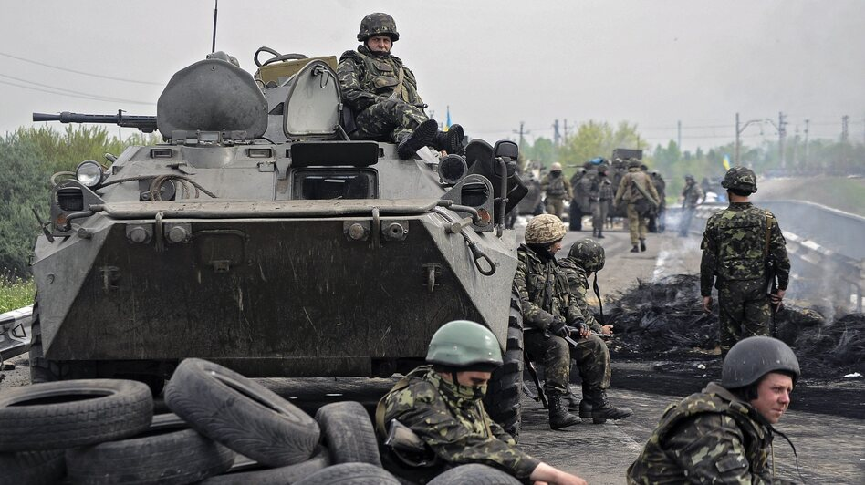 "Ukrainian soldiers stay near a checkpoint they seized not far from Slovyansk, Ukraine, on Friday. Ukrainian officials say two helicopters were shot down during an ""anti-terror"" operation against pro-Russia separatists."