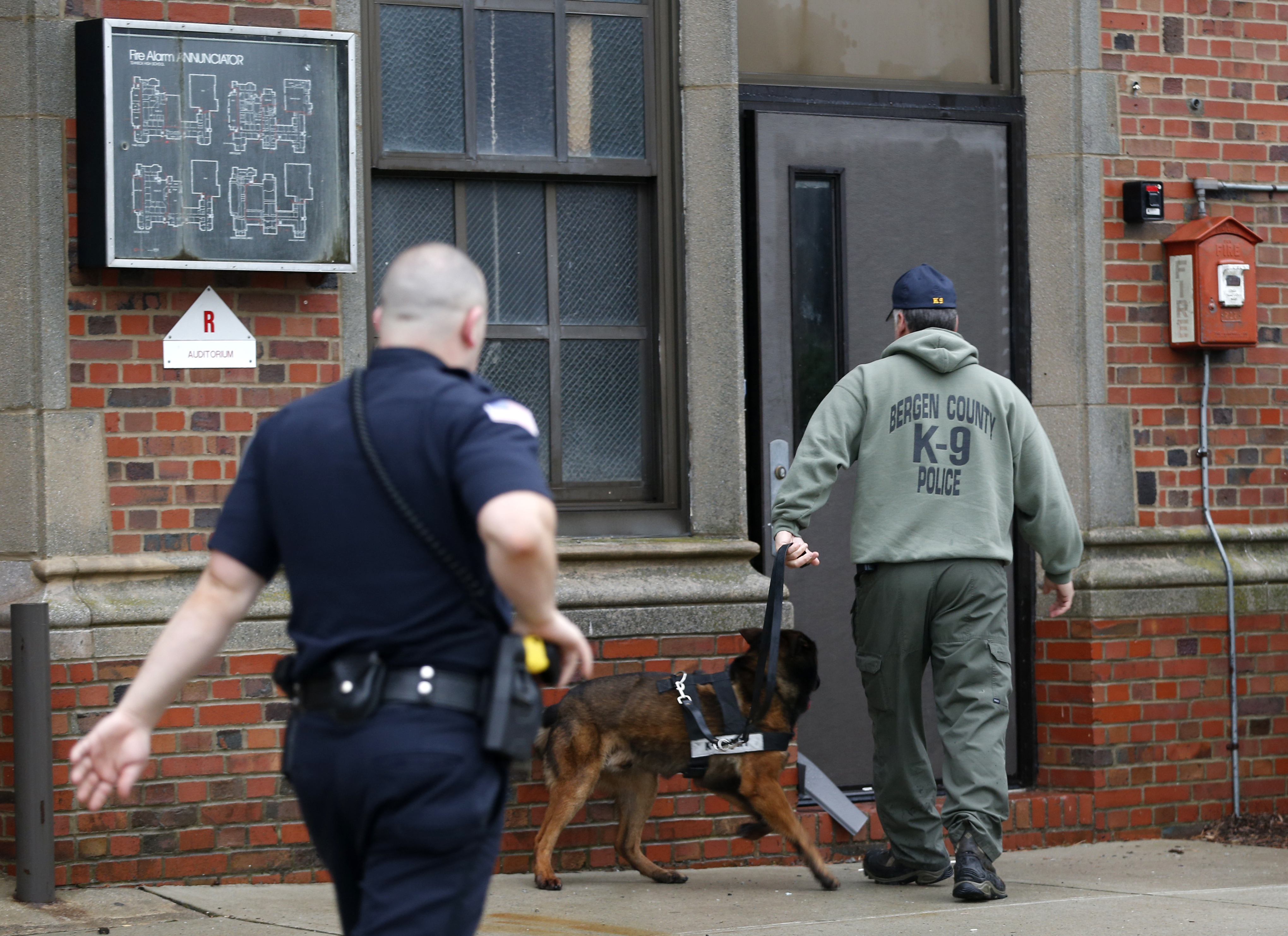 A Bergen County, N.J., police officer (right) walks with a police dog into  Teaneck High School, where 62 students were arrested during an overnight  break-in ...