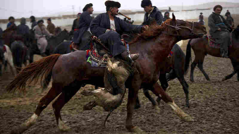 A chapandaz exhibits nearly perfect form: Whip in mouth, he hoists the buz — or ball — under his right leg and steers the horse with his left arm, during a round of buzkashi.