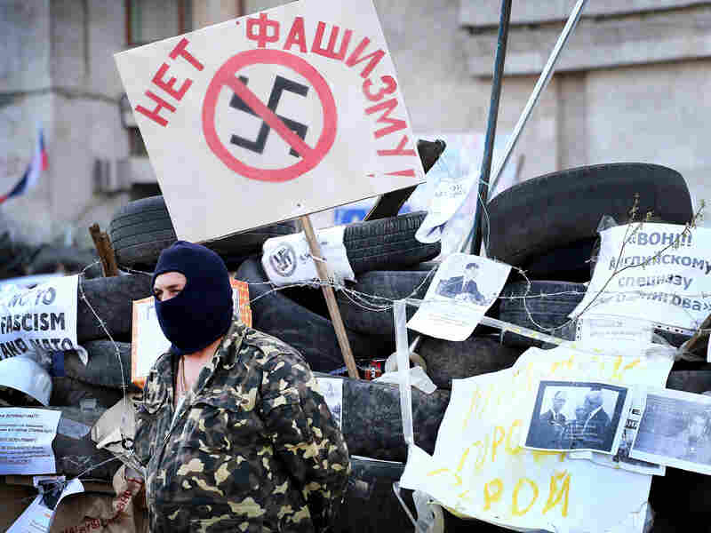 "A pro-Russian activist guards the Regional Administration building on April 18 in Donetsk, Ukraine. The placard behind him says, ""No to Fascism."""