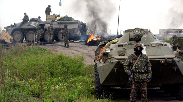 """Ukrainian soldiers stand at a checkpoint they seized Friday morning in the eastern Ukrainian village of Andreevka. The Russian government has referred to Ukraine's interim government and other Ukrainian groups as """"fascists"""" and """"neo-Nazis."""""""