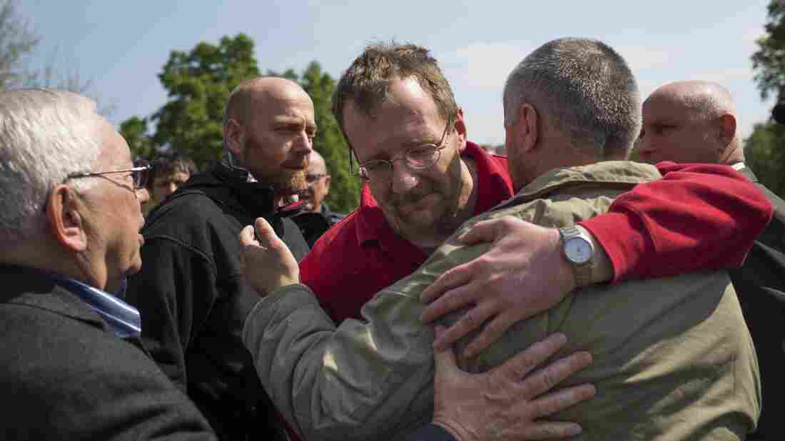 Military observers including German Col. Axel Schneider, second left, hug each other after being released in Slovyansk, eastern Ukraine, Saturday. They were released to Russian envoy Vladimir Lukin, left.