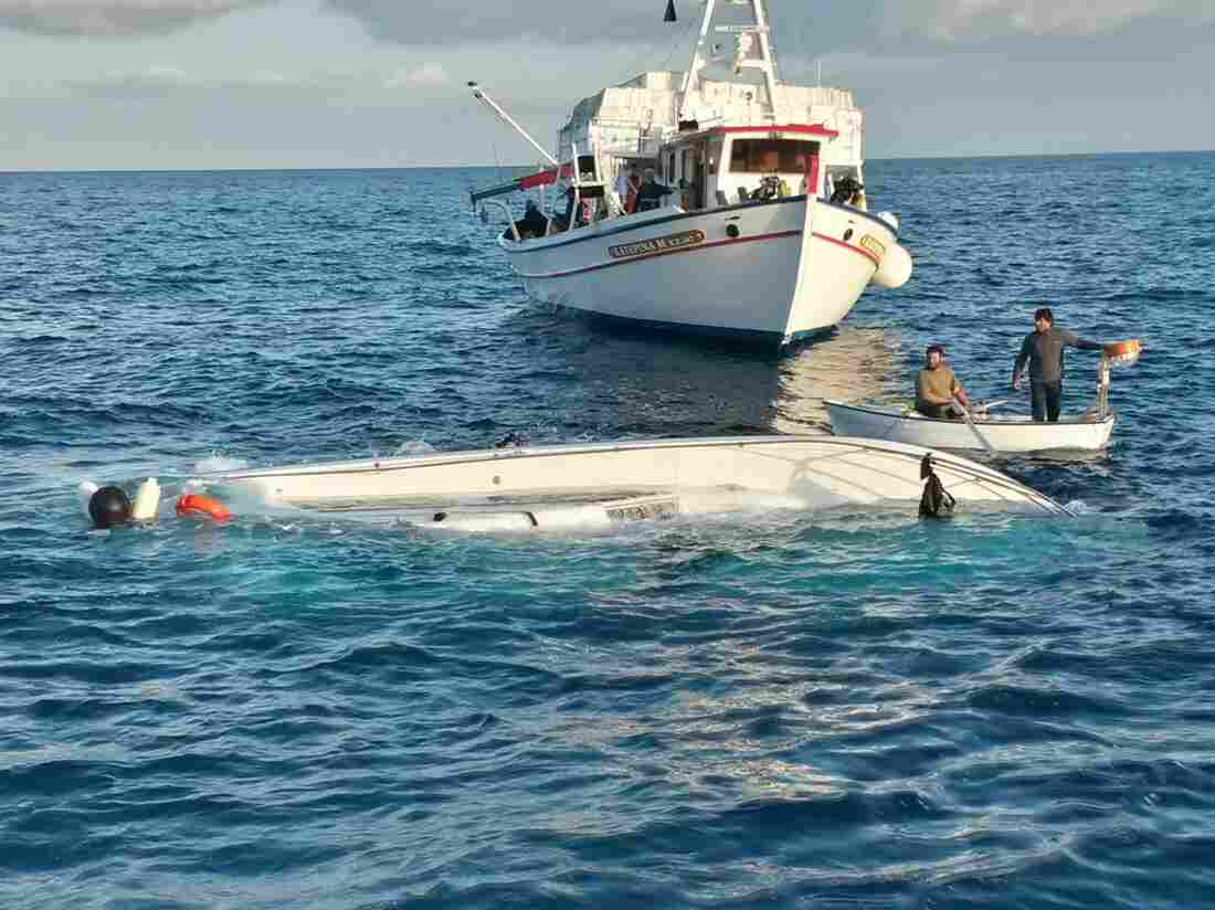 A handout photo provided by the Hellenic coast guard shows local fishermen examining a yacht that sank off the eastern Aegean island of Samos, Greece, on Monday.