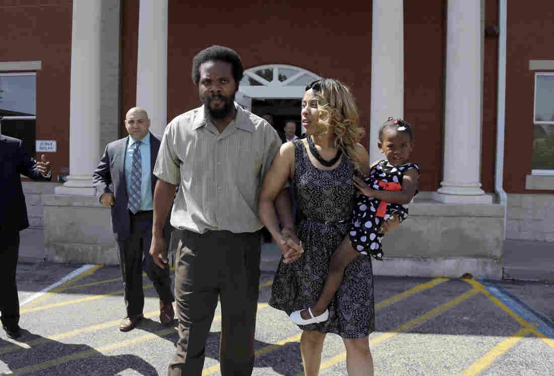 """Cornealious """"Mike"""" Anderson walks out of the Missouri County Courthouse along with his wife, LaQonna Anderson, their daughter Nevaeh, 3, and his attorney Patrick Megaro on Monday in Charleston, Mo."""