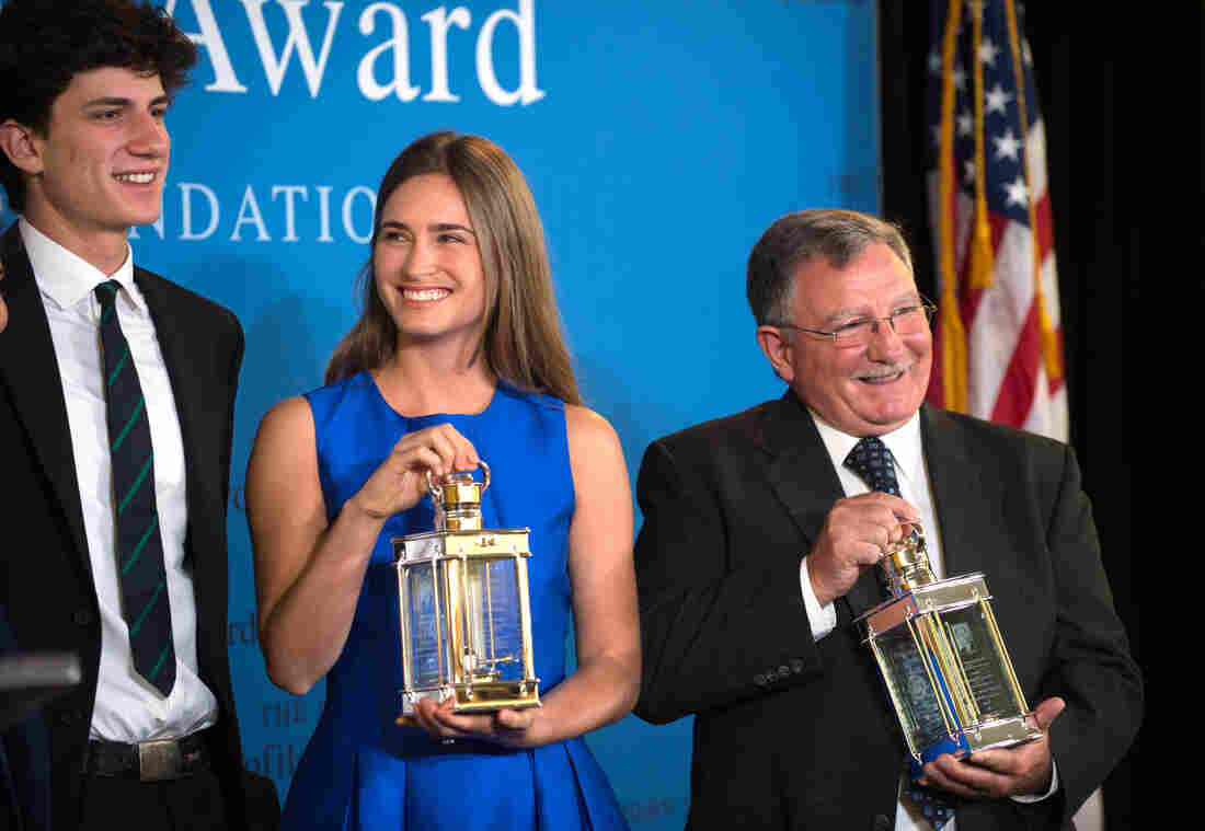 Accepting the 2014 John F. Kennedy Profile in Courage Award on behalf of her grandfather former President George H.W. Bush, Lauren Bush Lauren, center, and fellow Award recipient Paul W. Bridges, the former mayor of Uvalda, Ga., right, hold the awards as they stand with Jack Schlossberg, left, grandson of President John F. Kennedy.