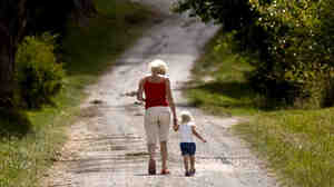 An adult and a child walk down a gravel road.
