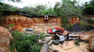 People survey the damage on Scenic Highway in Pensacola, Fla., after part of it collapsed following heavy rains and flash flooding on April 30.