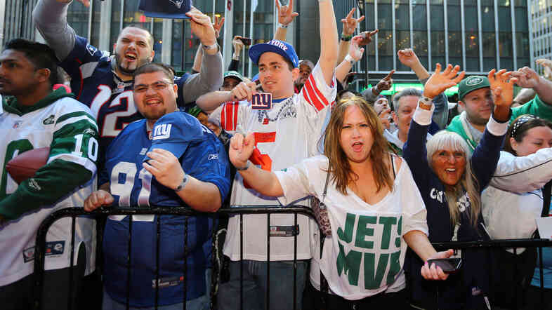 Fans outside Radio City Music Hall show support for their teams during the first round of the 2013 NFL Draft on April 25, 2013, in New York.