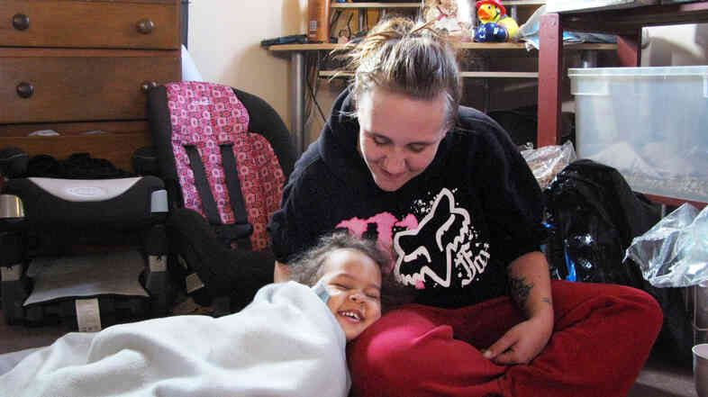 Desiree Metcalf, here with one of her three daughters, is one of many poor Americans who find themselves trapped in a system meant to help.