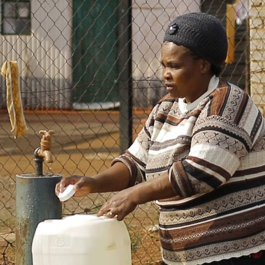 A women fills up water buckets in front of an election billboard near Johannesburg on Tuesday. Opposition political parties, like the one featured here, say that corruption is a major problem in the ruling African National Congress.